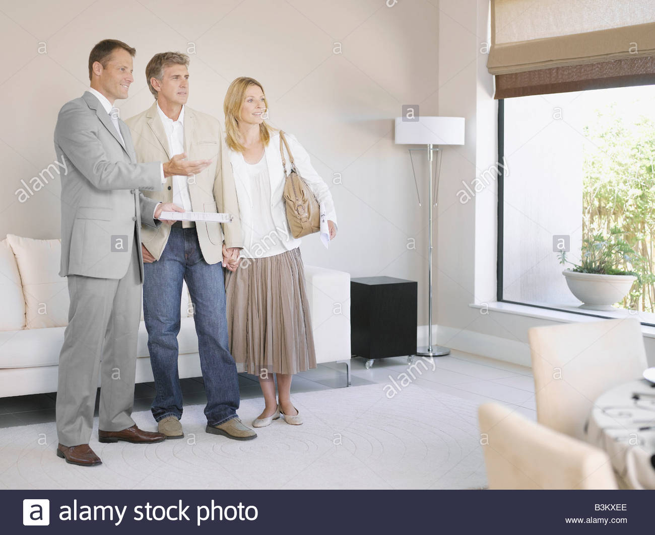 Real estate agent showing couple new home - Stock Image
