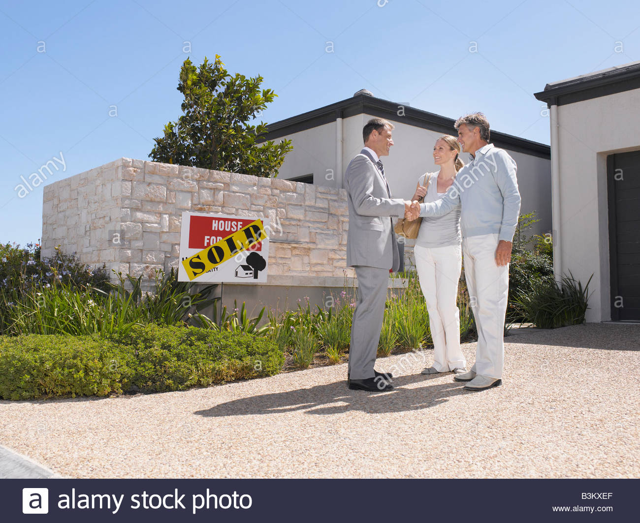 Couple shaking hands with real estate agent at new home - Stock Image