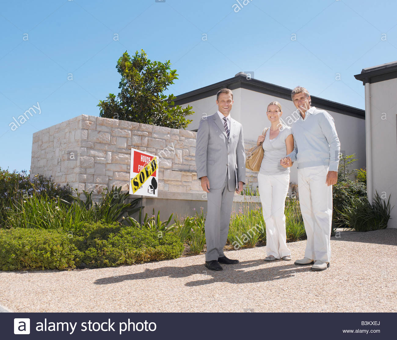 Couple with real estate agent at new home - Stock Image