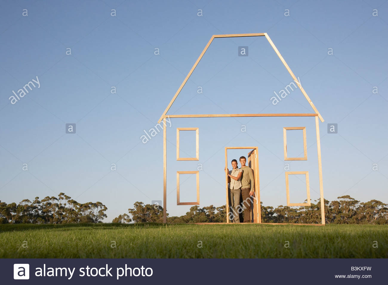 Couple in doorway of house outline - Stock Image