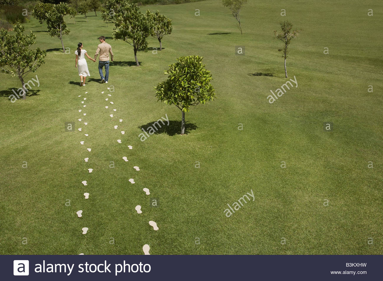 Couple walking through field trailing footprints Stock Photo