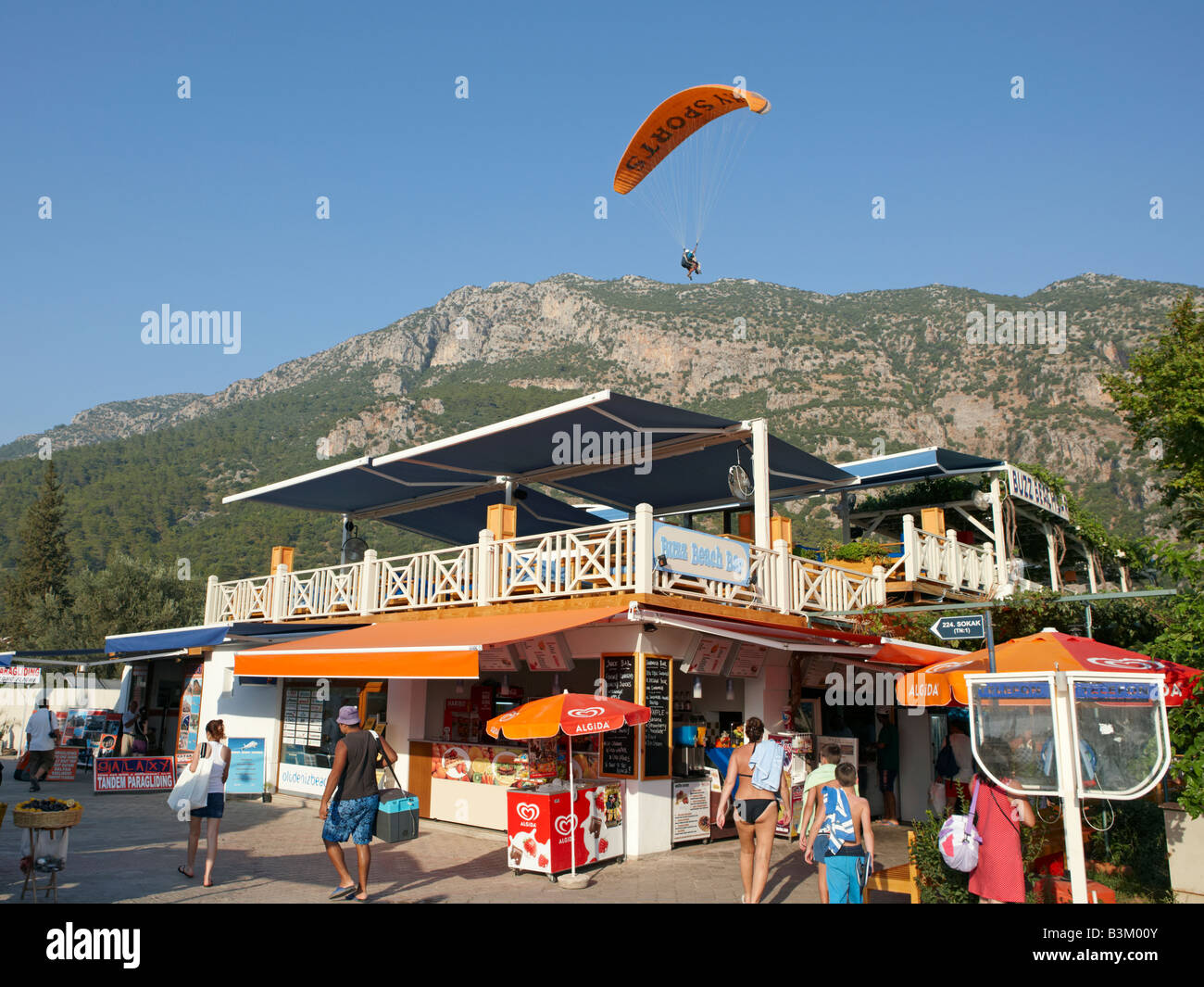 Paraglider flying above the popular Buzz Bar in the village of Oludeniz. Province of Mugla, Turkey. Stock Photo