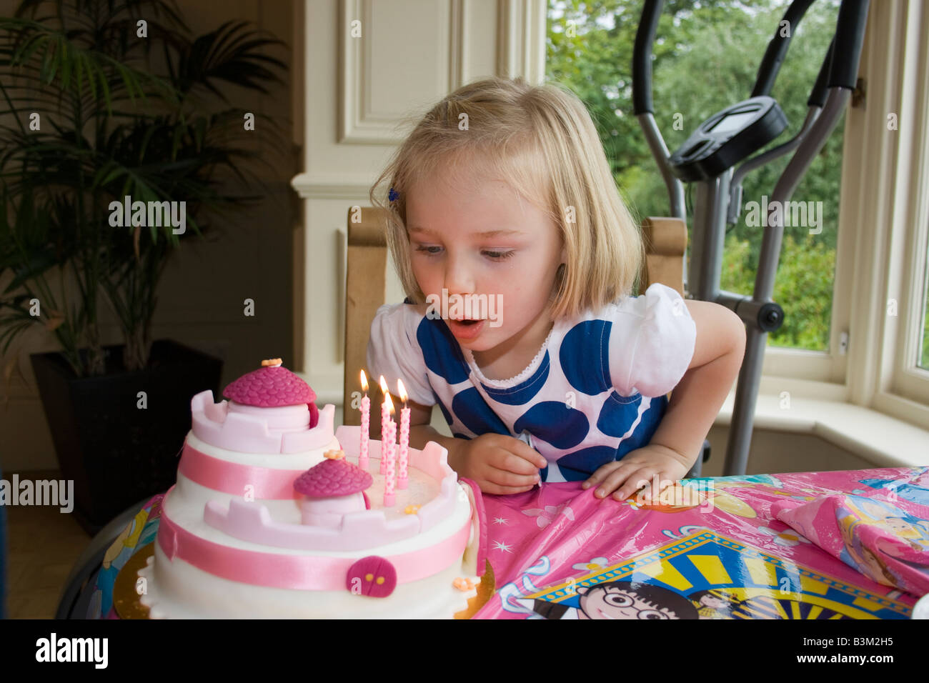 UK 4 Year Old Girl Blowing Out Candles On Birthday Cake