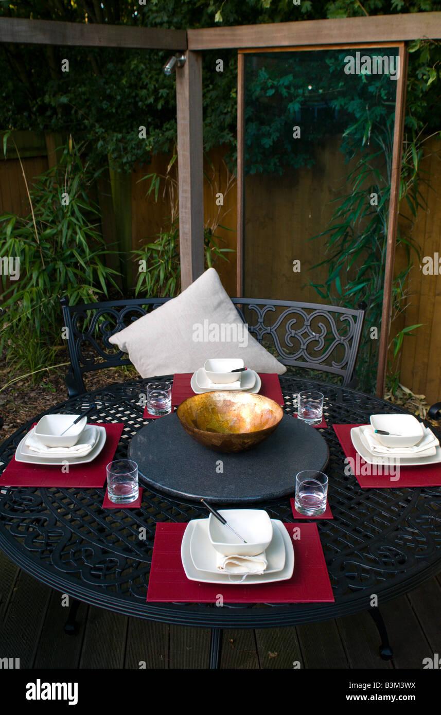 outdoor dining set in modern landscaped garden Stock Photo
