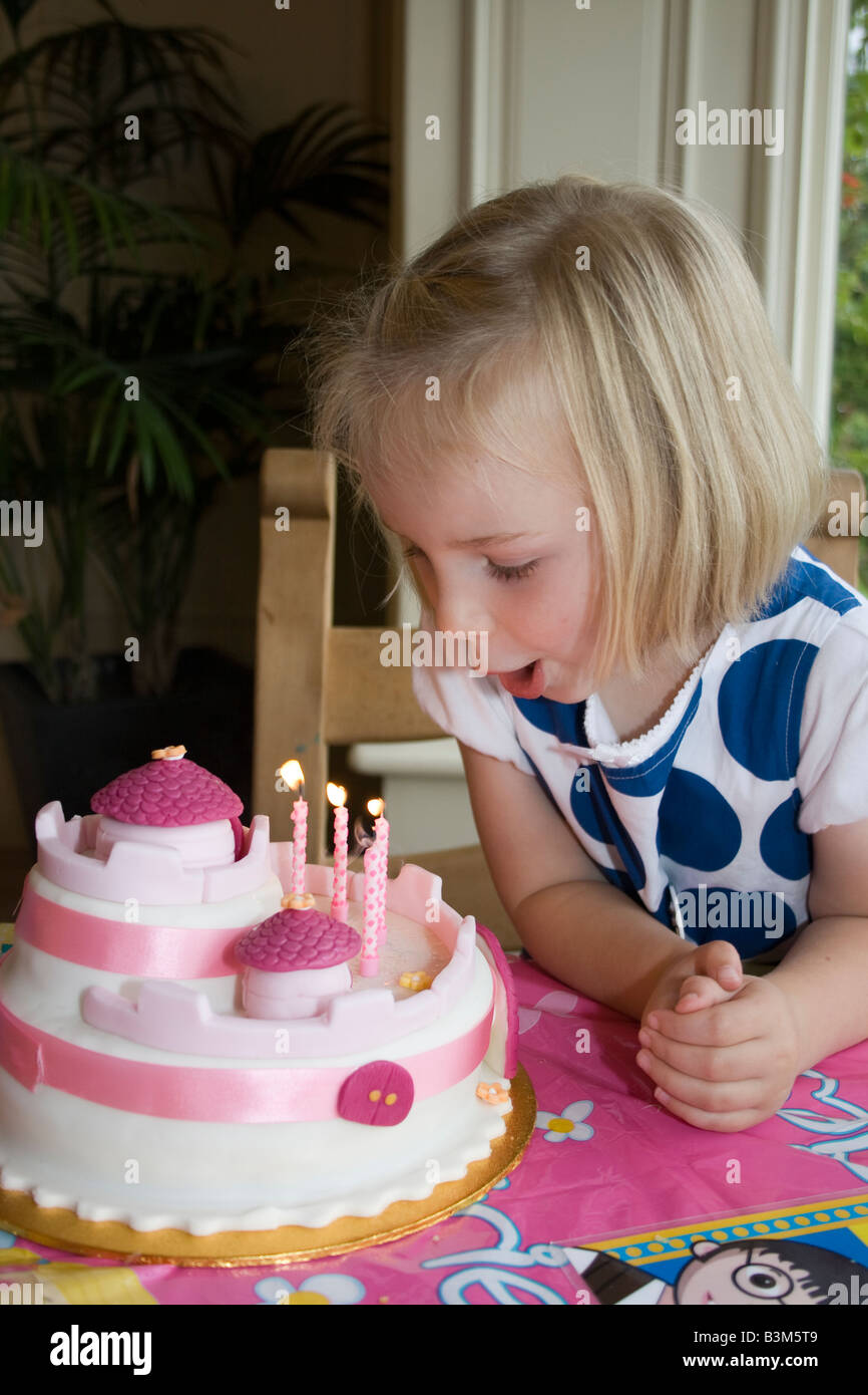 Wondrous Uk 4 Year Old Girl Blowing Out Candles On Birthday Cake Stock Personalised Birthday Cards Veneteletsinfo