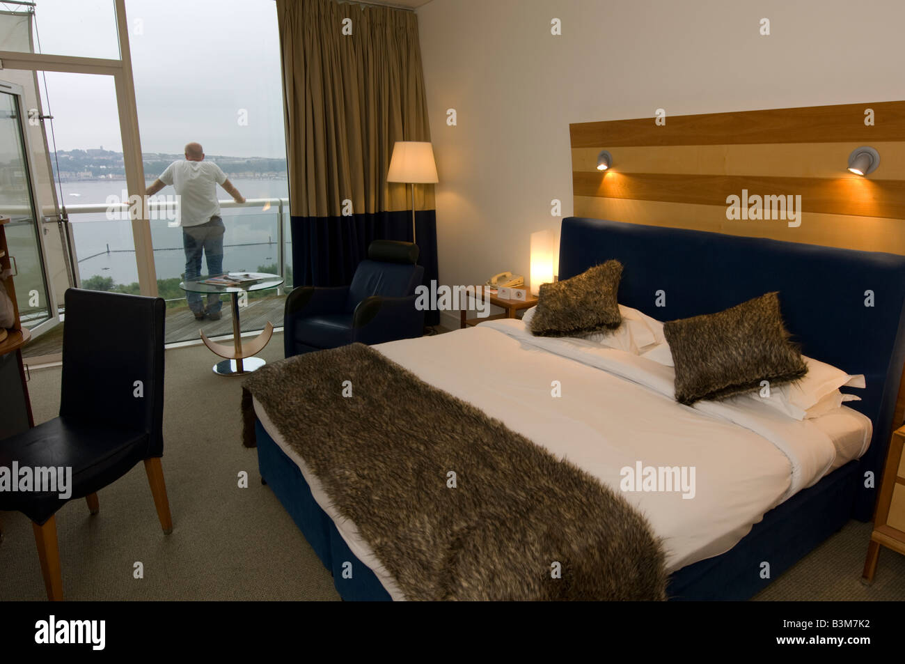 Bedroom at the St Davids luxury 5 star hotel Cardiff bay Wales UK - man standing on balcony looking at the view - Stock Image