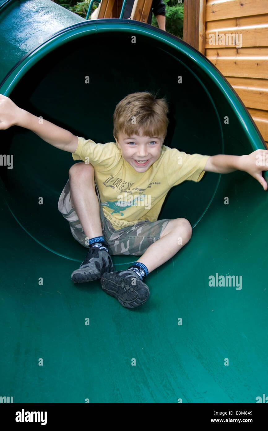 6 year old boy on slide - Stock Image