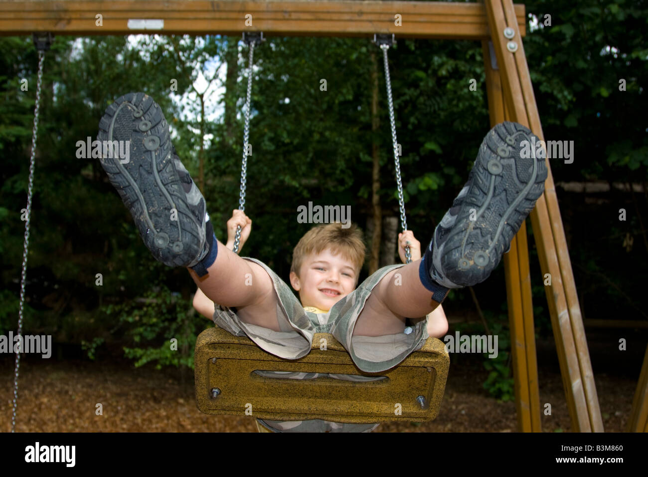 6 year old boy on swing - Stock Image