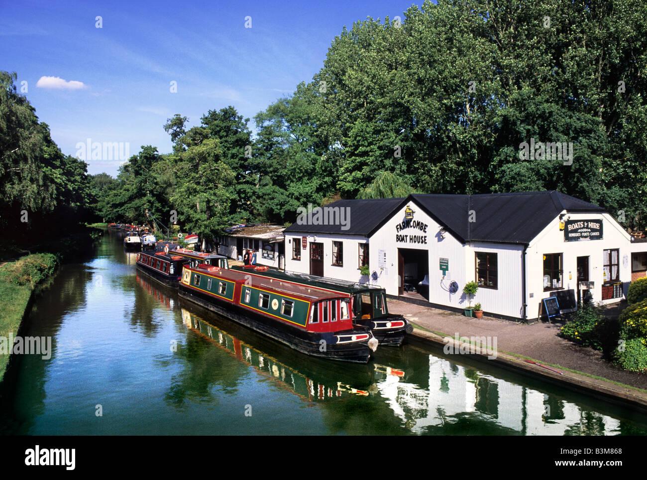 Narrow boats moored at Farncombe Boathouse, River Wey Navigation, near Godalming Surrey - Stock Image