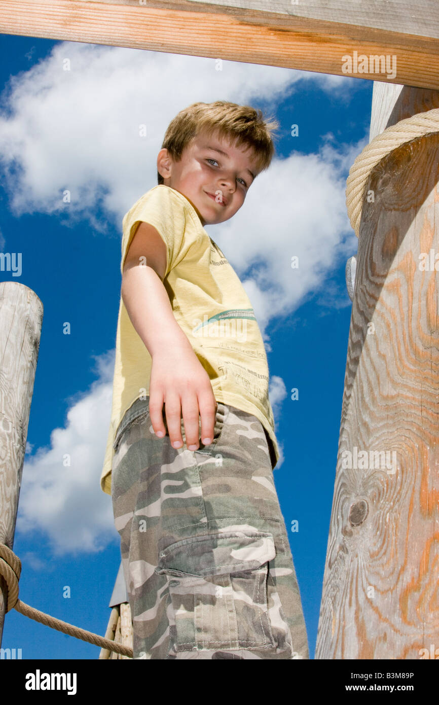 6 year old boy on wooden climbing frame - Stock Image
