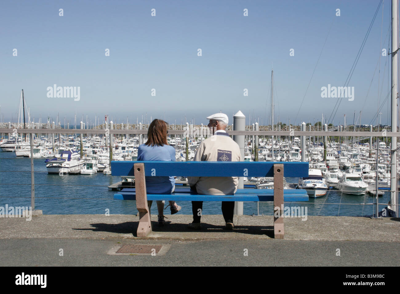 Nautical scene with elderly man and younger woman sitting together on bench seat overlooking harbour with boats - Stock Image