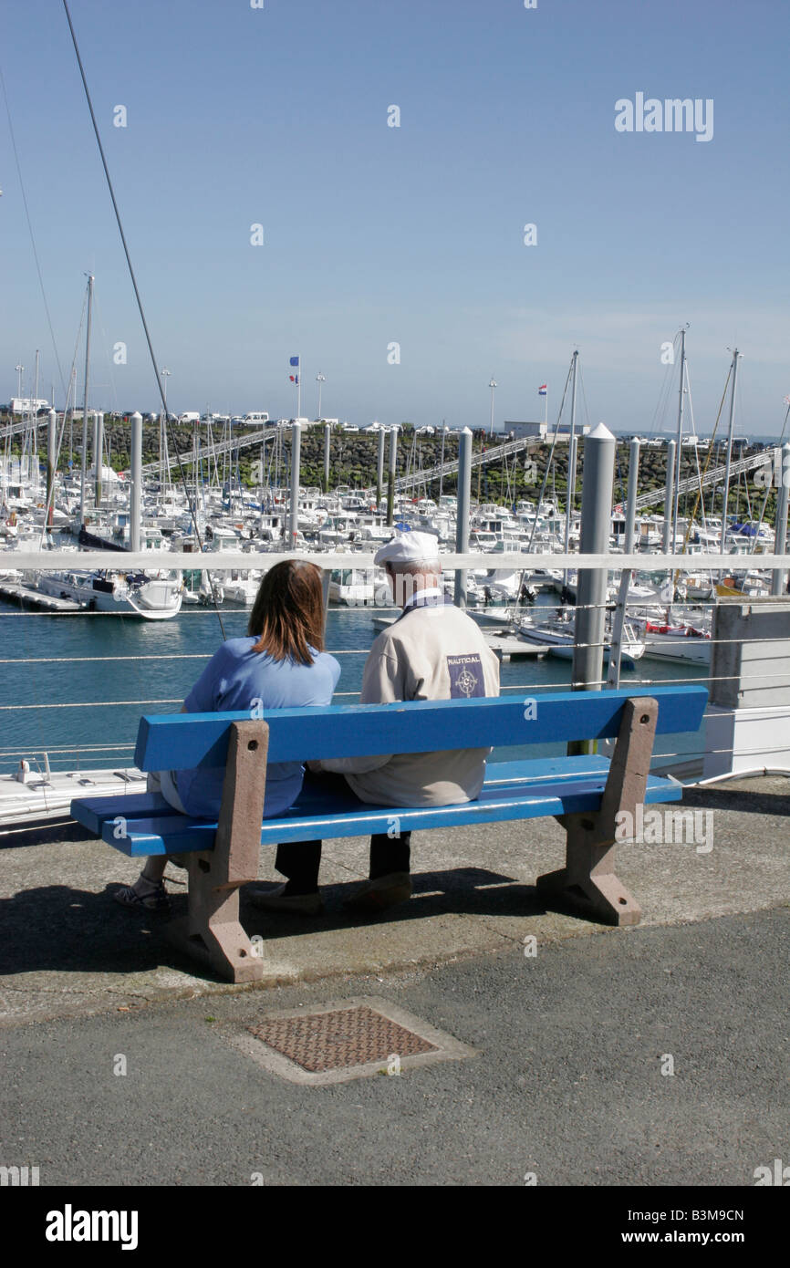 Nautical scene with elderly man and younger woman sitting together on bench seat overlooking harbour with boats Stock Photo