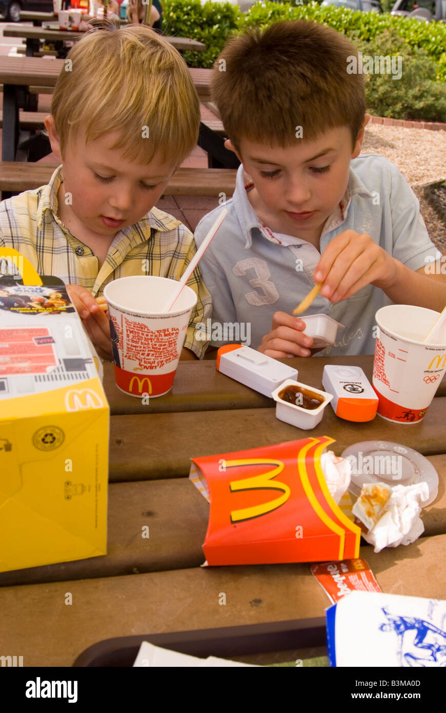 Two boys eating Happy Meals at Mcdonald's - Stock Image