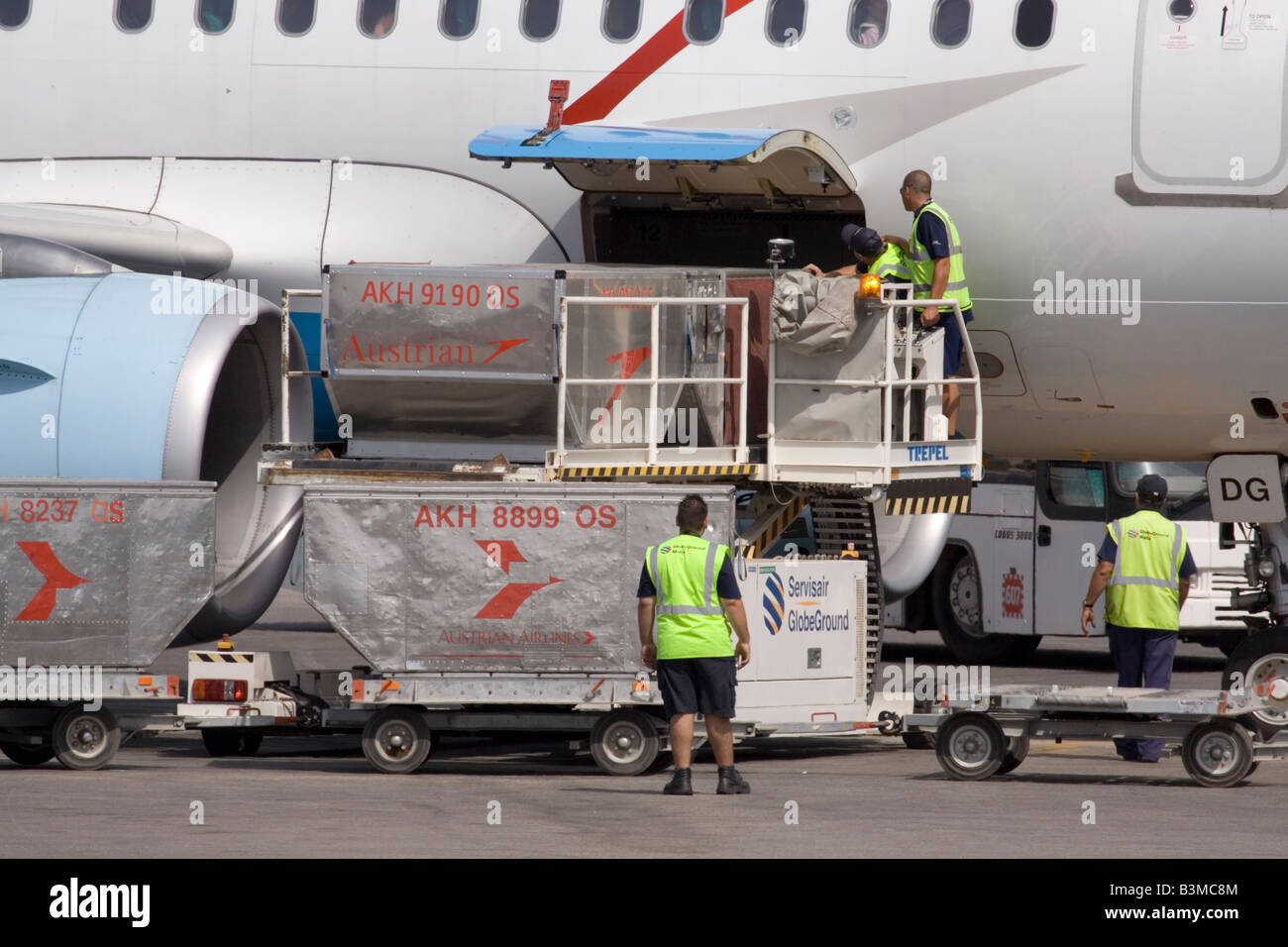 Commercial air freight transport. Loading cargo on board an Austrian Airlines Airbus A319 passenger jet plane - Stock Image