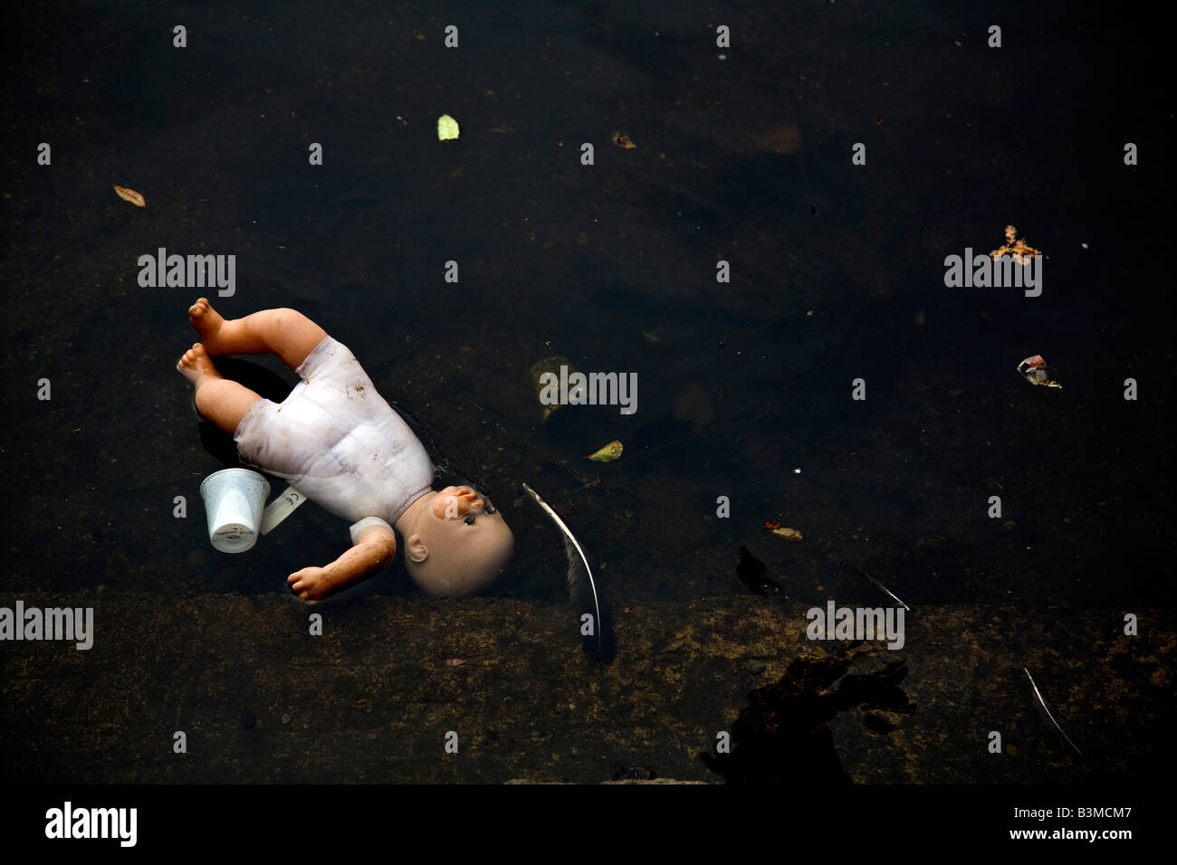 Discarded childrens doll in water with rubbish - Stock Image