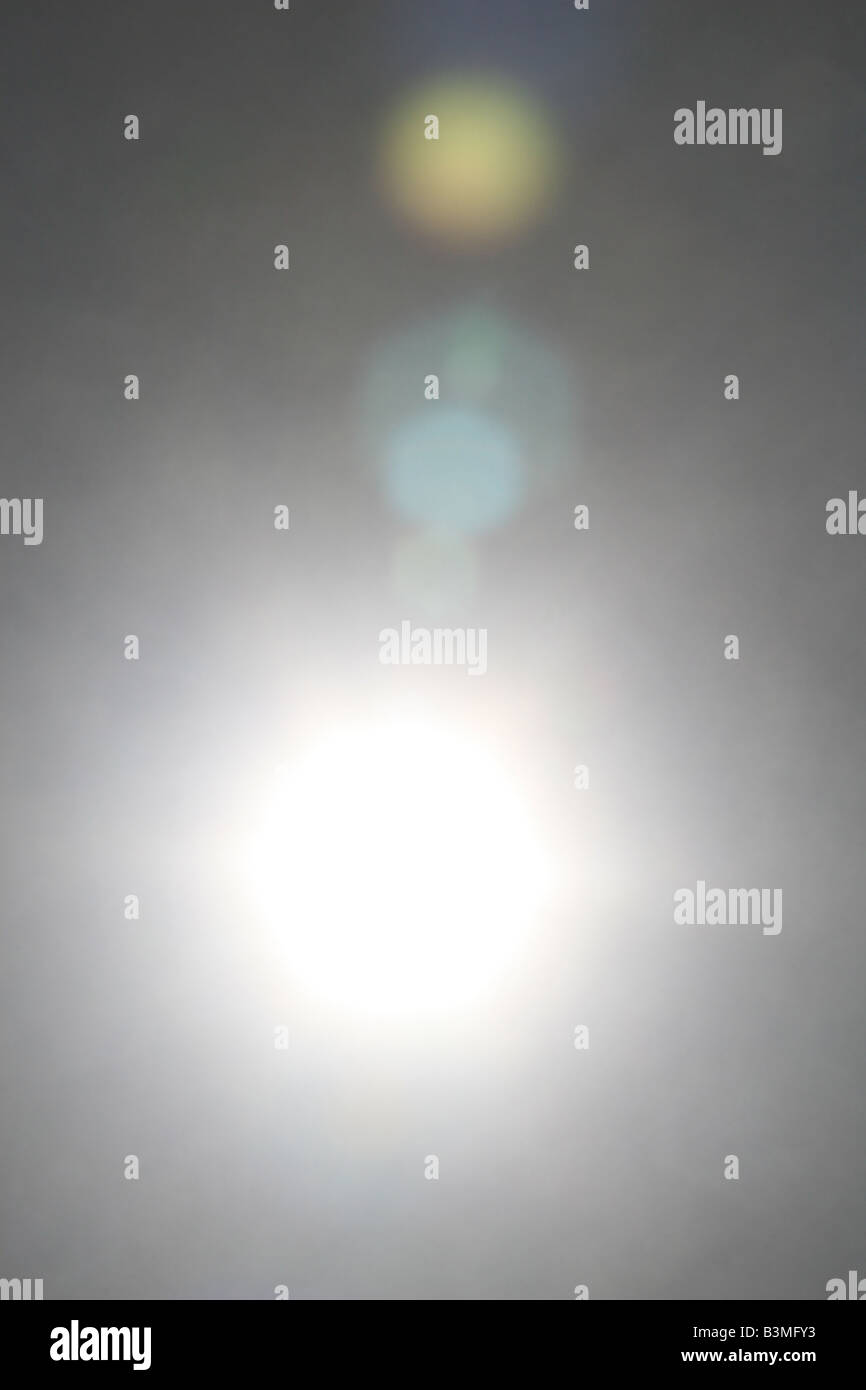 Lens flare looking in the sun, with a partial spectrum of colors visible. - Stock Image