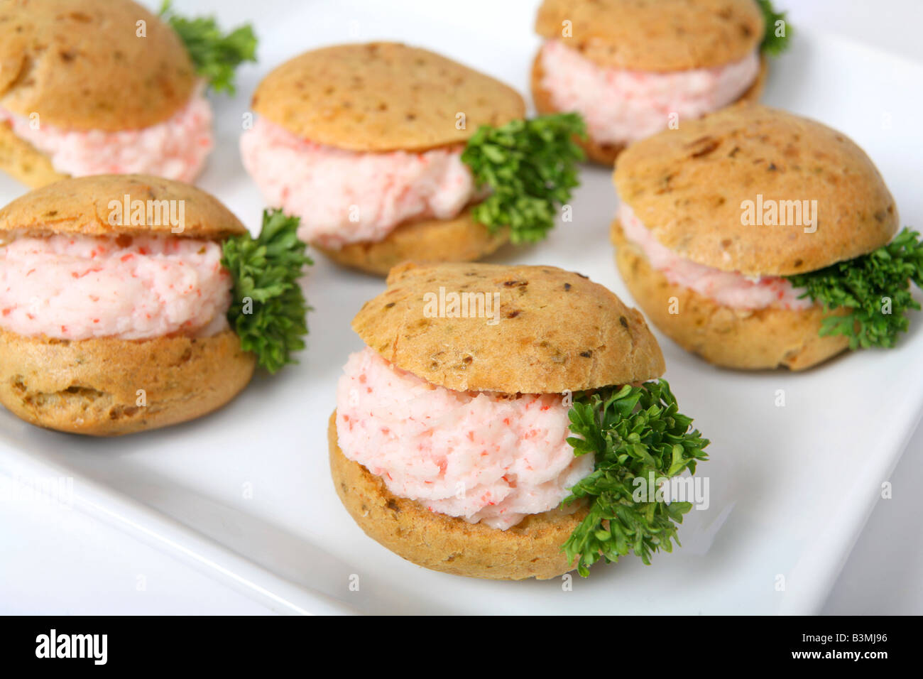 A pureed prawn meat filling in small brown bread canapes on a plate - Stock Image
