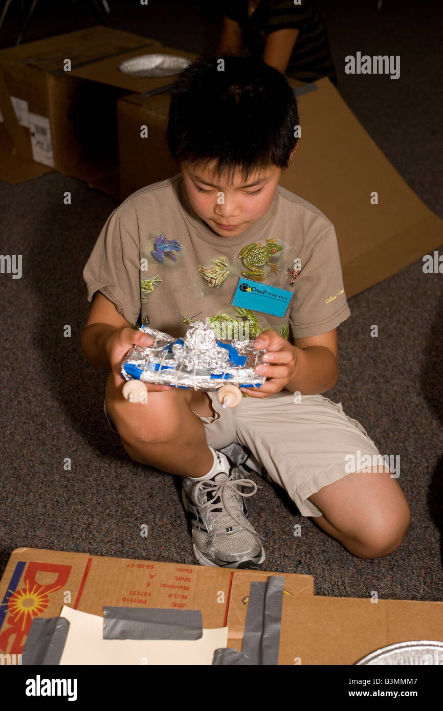 ten year old boy working on model vehicle made of recycled materials at school - Stock Image