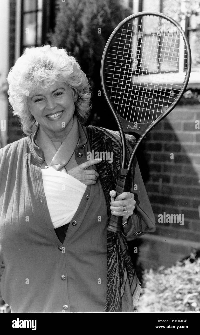 Gloria Hunniford TV Presenter holding the tennis racket she was useing when she broke her arm Her arm is still in - Stock Image