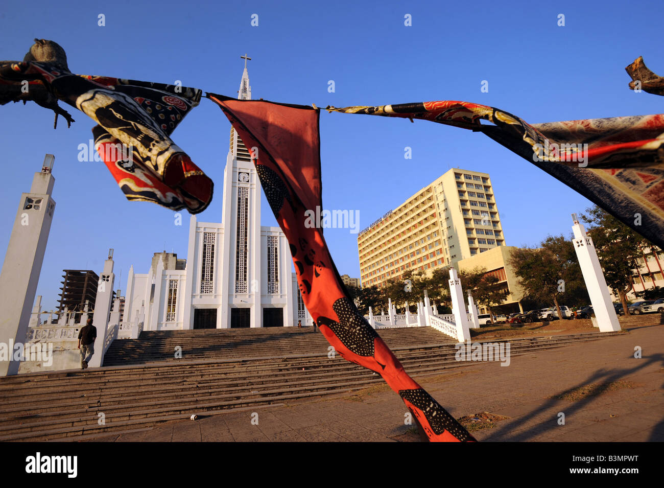 Batiks flutter in the breeze outside the hotel Rovuma and the catholic cathedral of Nossa Senhora da Conceicao in Stock Photo