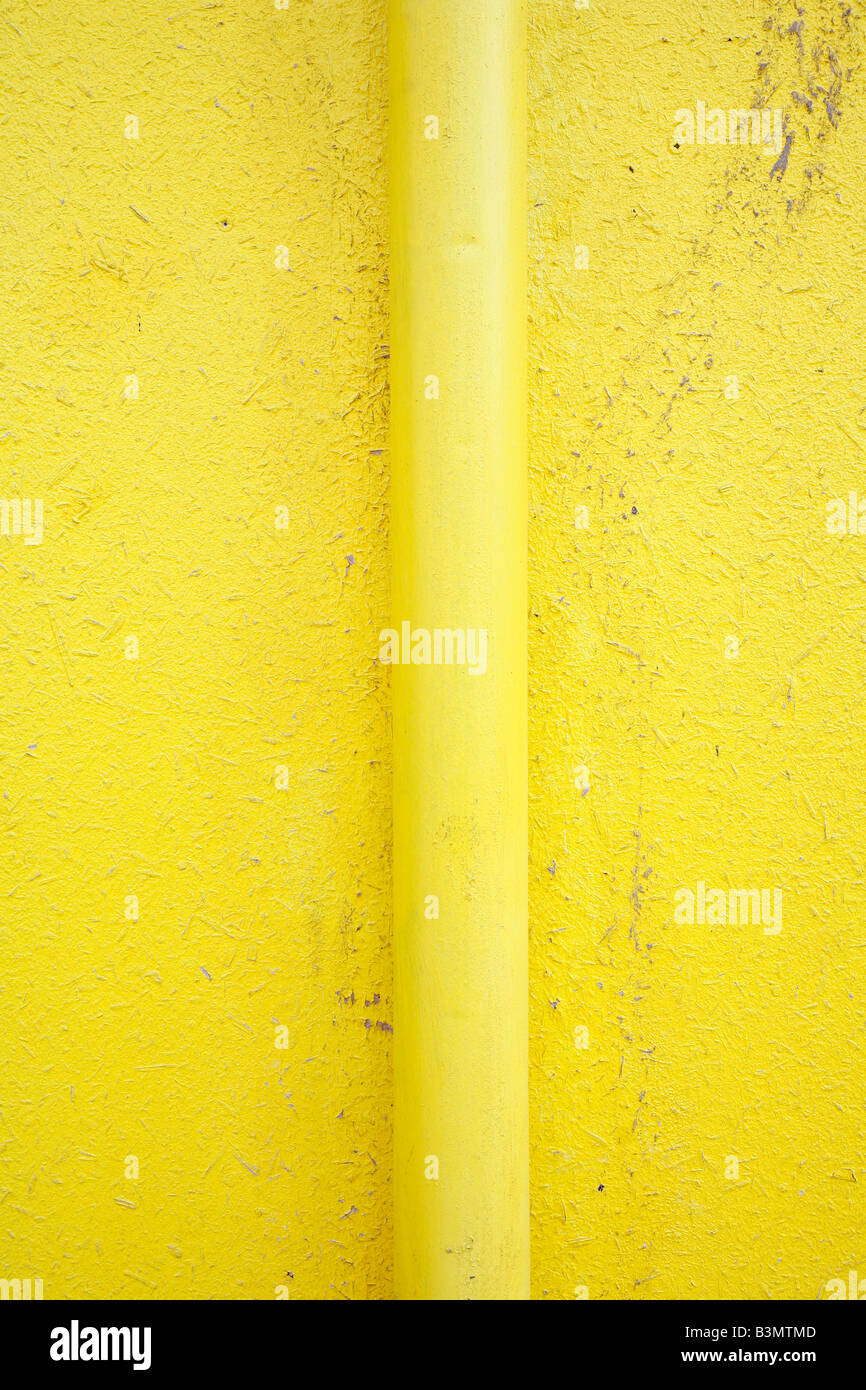 Pipe on yellow wall - Stock Image
