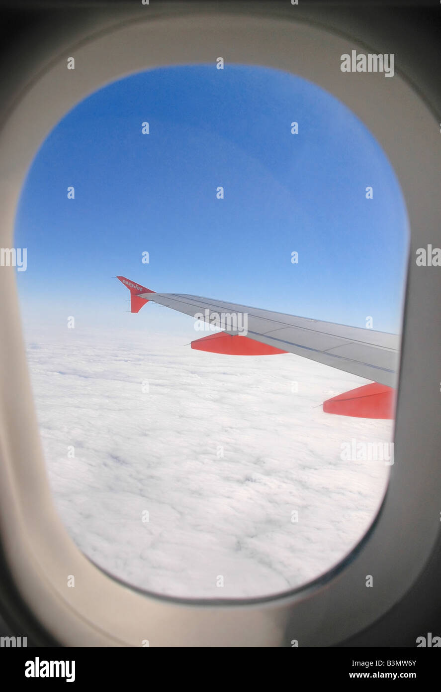 The wings of a passenger airliner and land and clouds as seen from the plane window. - Stock Image