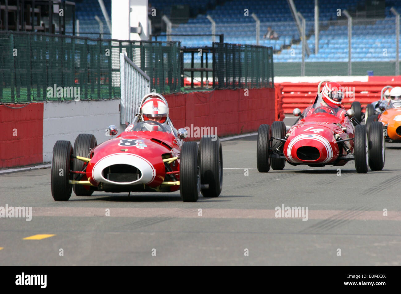 two red racing cars crossing the starting line Stock Photo