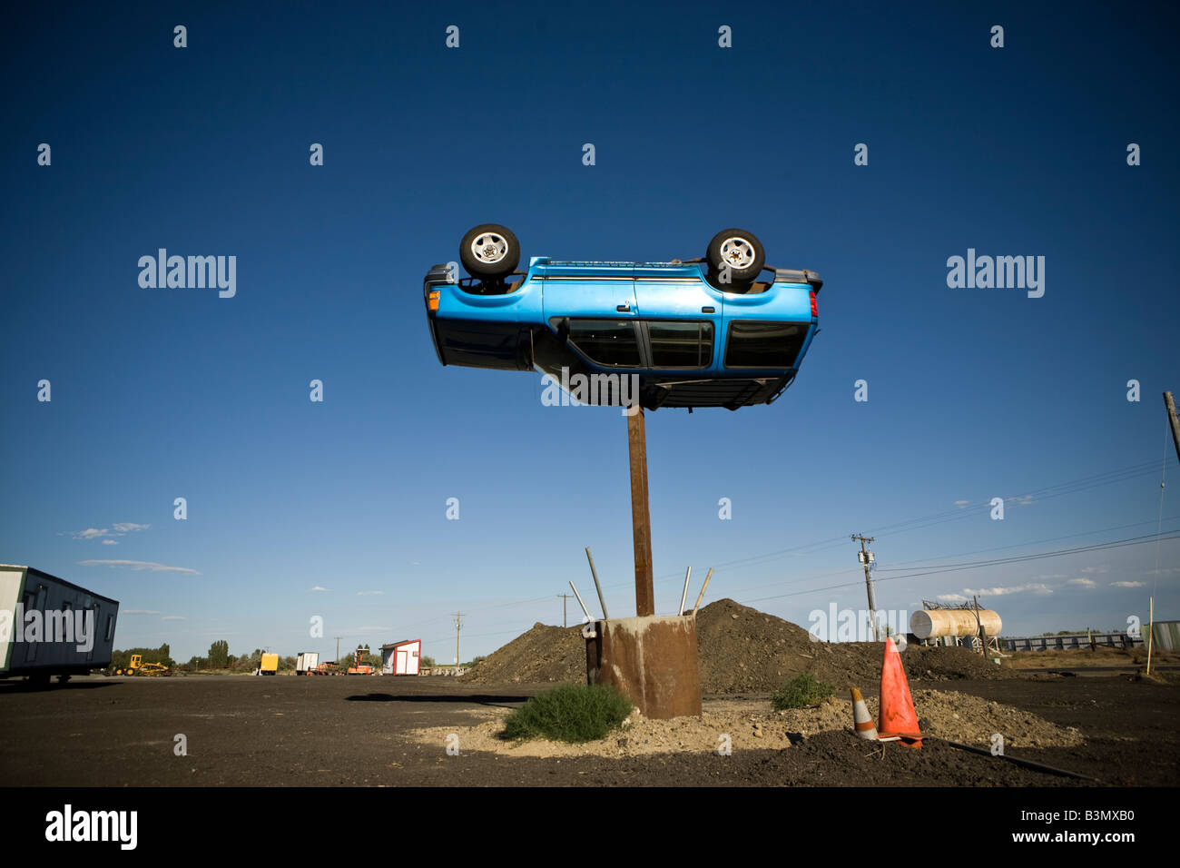 A Ford Explorer SUV turned upside down sits atop a 15 feet high metal column. - Stock Image