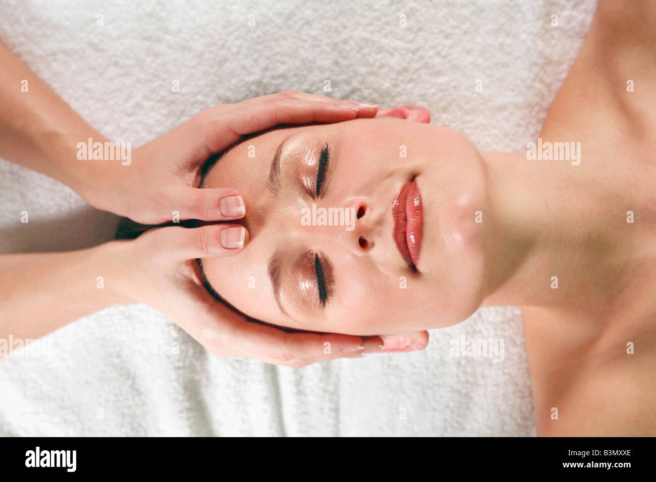 Young woman receiving facial massage, eyes closed, elevated view Stock Photo