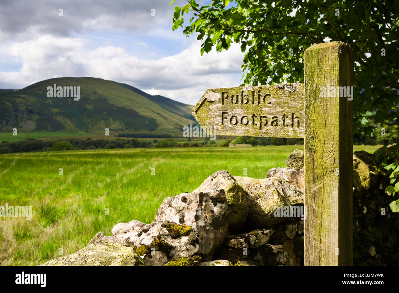 Wooden public footpath signpost sign and dry stone wall overlooking Lake District mountains in Cumbria, England, - Stock Image
