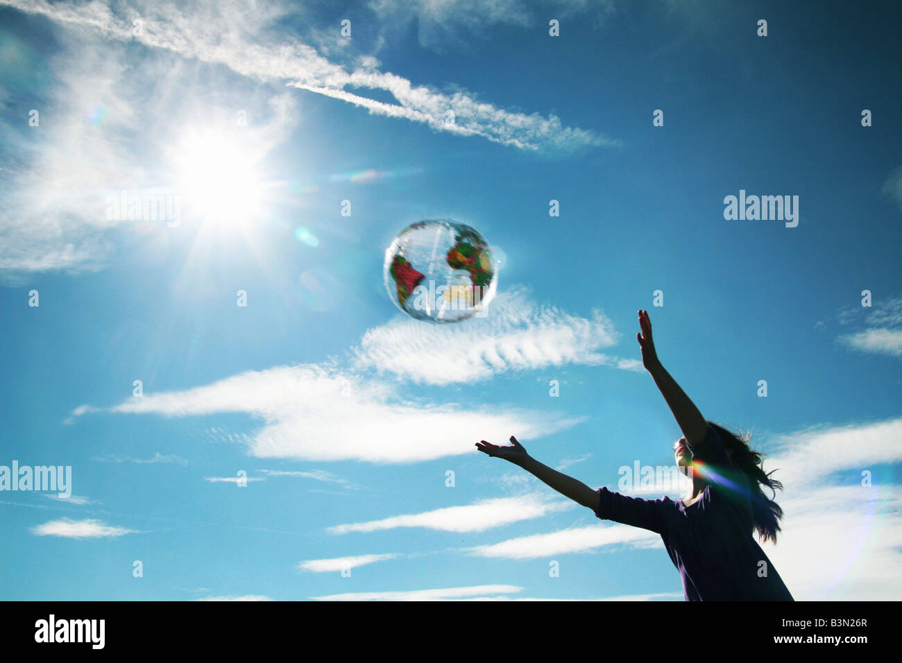 girl catching an inflatable globe - Stock Image