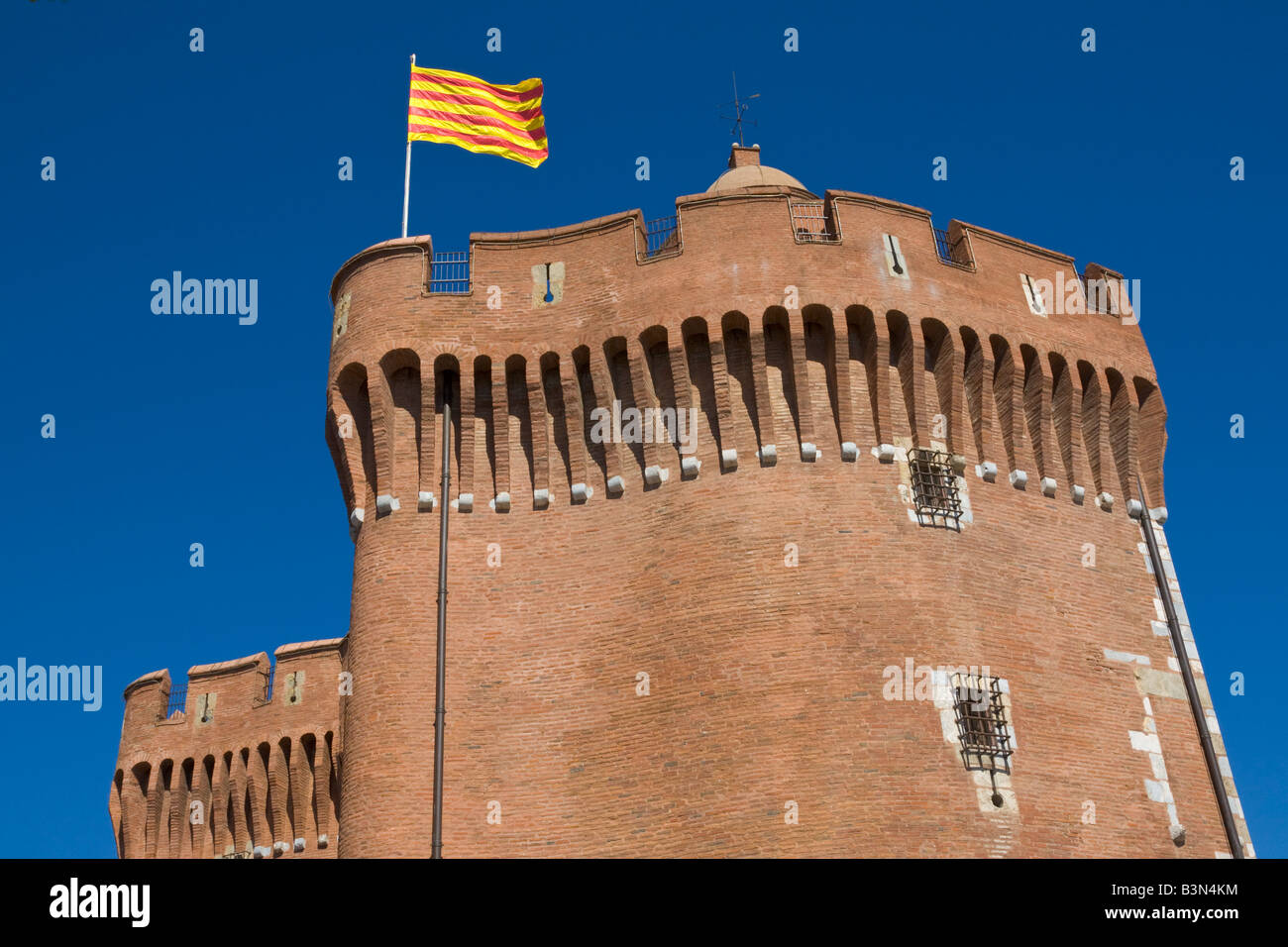 The Catalonian flag is blowing above the city gate 'Le Castillet'  in midtown Perpignan / Southern France - Stock Image
