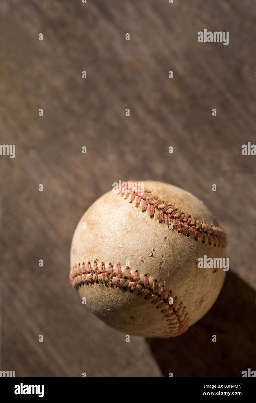 A scuffed and used baseball after hard use - Stock Image