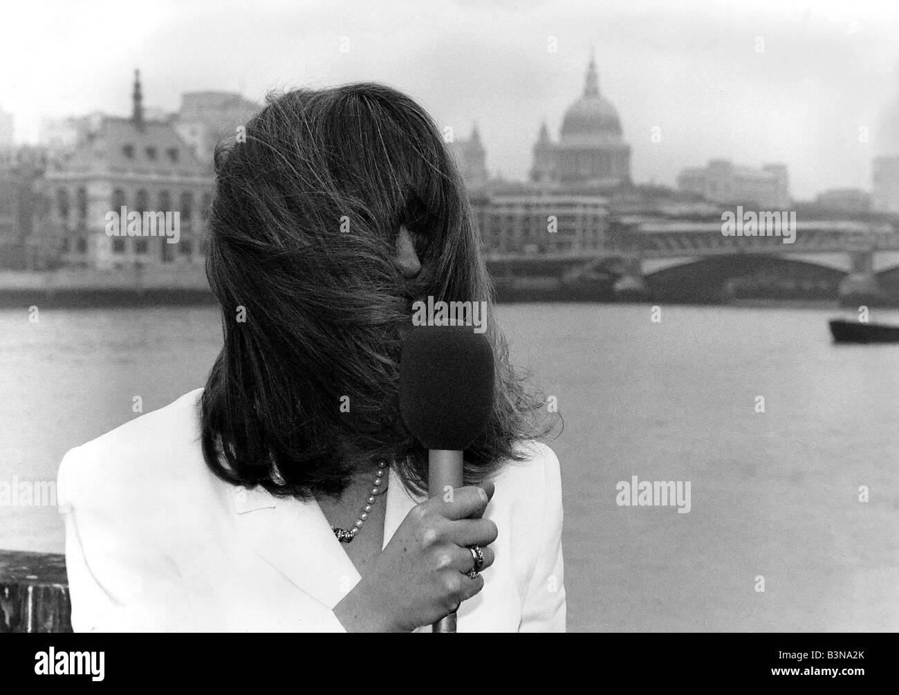 Caron Keating TV Presenter holding microphone hair blowing over her face - Stock Image