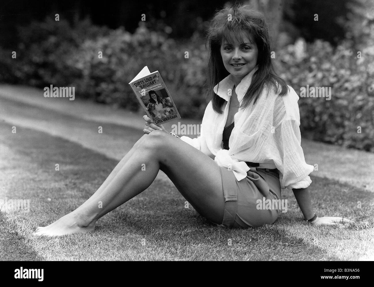 Carol Vorderman TV Presenter sitting on grass lawn holding paperback book - Stock Image