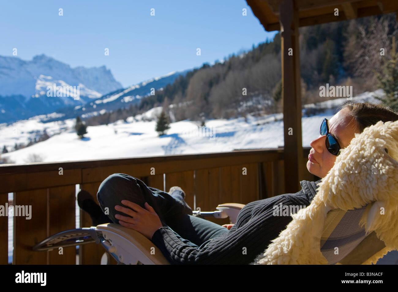 Switzerland, Graubuenden, Savognin, woman relaxing on sun terrace - Stock Image