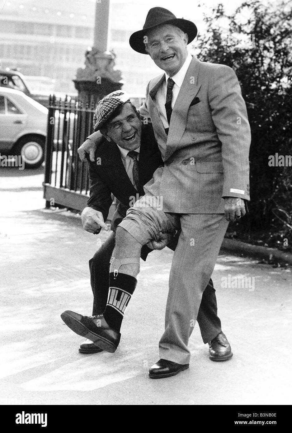 Ernie Wise with Noman Wisdom showing off his legs at the International Men s Boy s wear exhibition February 1989 - Stock Image