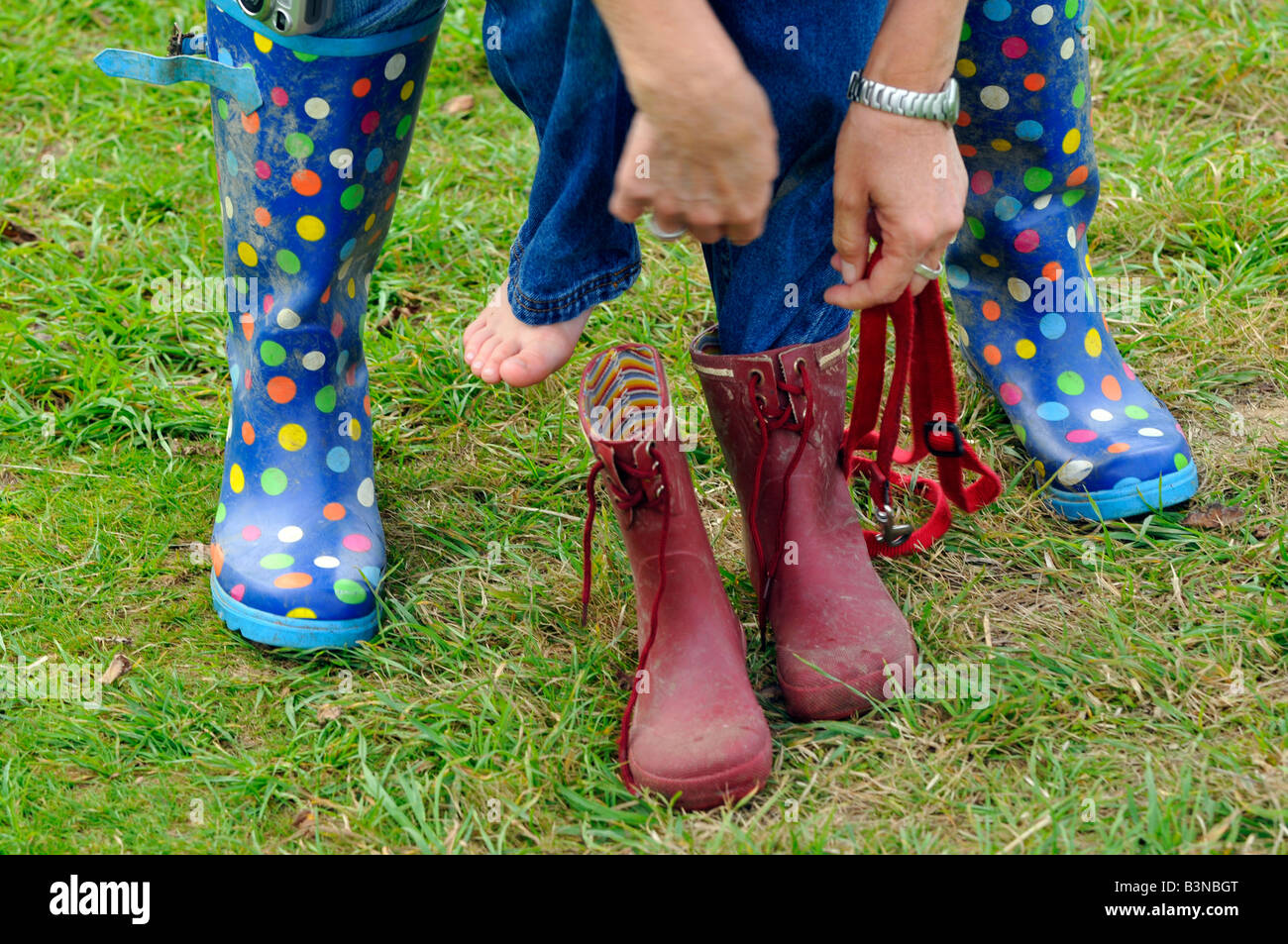 mother trying to put shoes boots on child wellies mother and child struggling to get child children dressed - Stock Image
