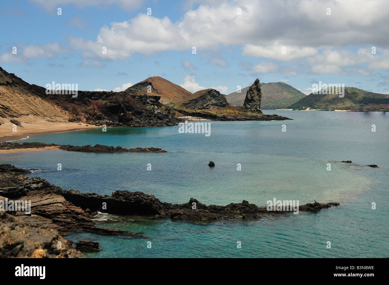 A view of the famous Pinnacle Rock at Bartolome Island, Galapagos. Tropical blue waters and a rocky circular pool - Stock Image