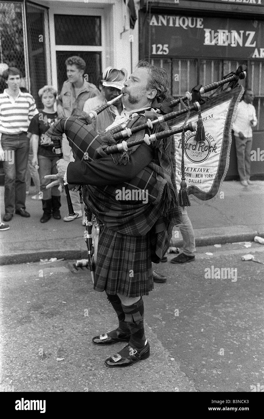 Notting Hill Carnival August 1987 A Scottish bag pipe player plays to residents in the street of Notting Hill - Stock Image