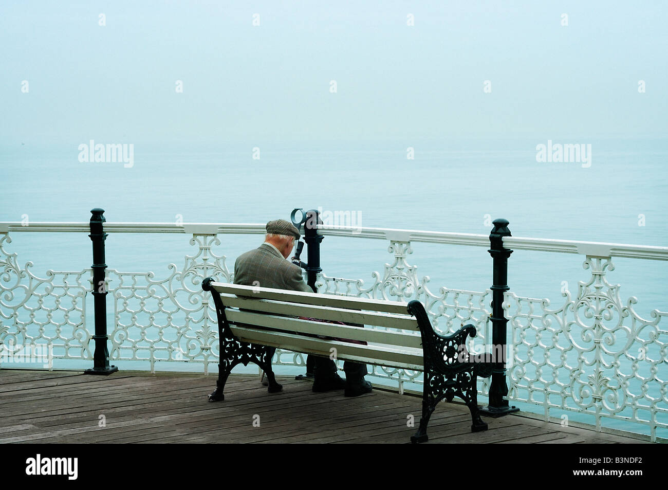 Senior man wearing tweed jacket and cap sits on a bench overlooking the ocean on Brighton Pier Brighton England - Stock Image