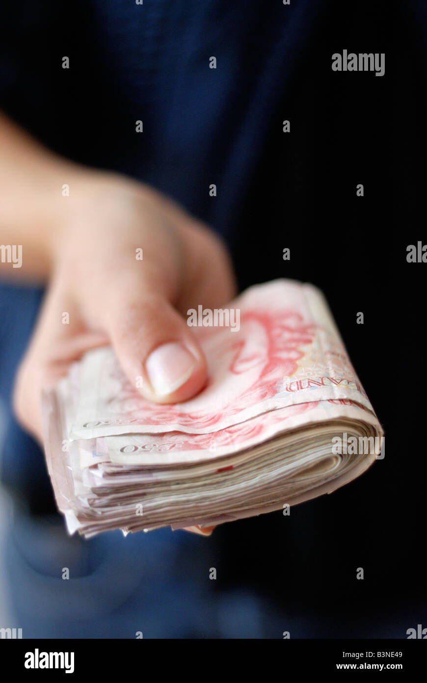 UK currency person handing a wad of fifty pound notes close up - Stock Image