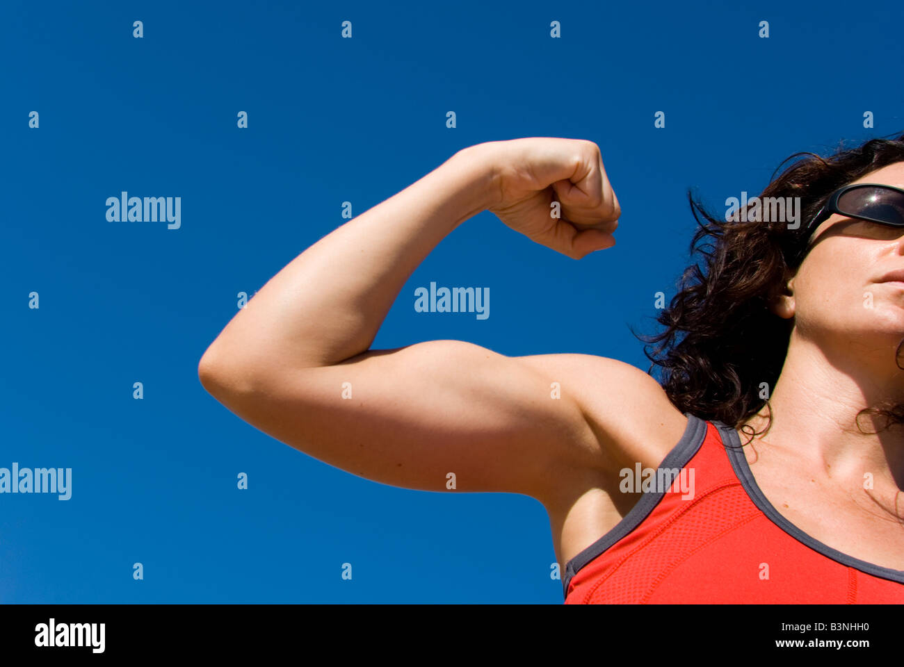 Model Released sporty female flexing biceps against a clear blue sky - Stock Image
