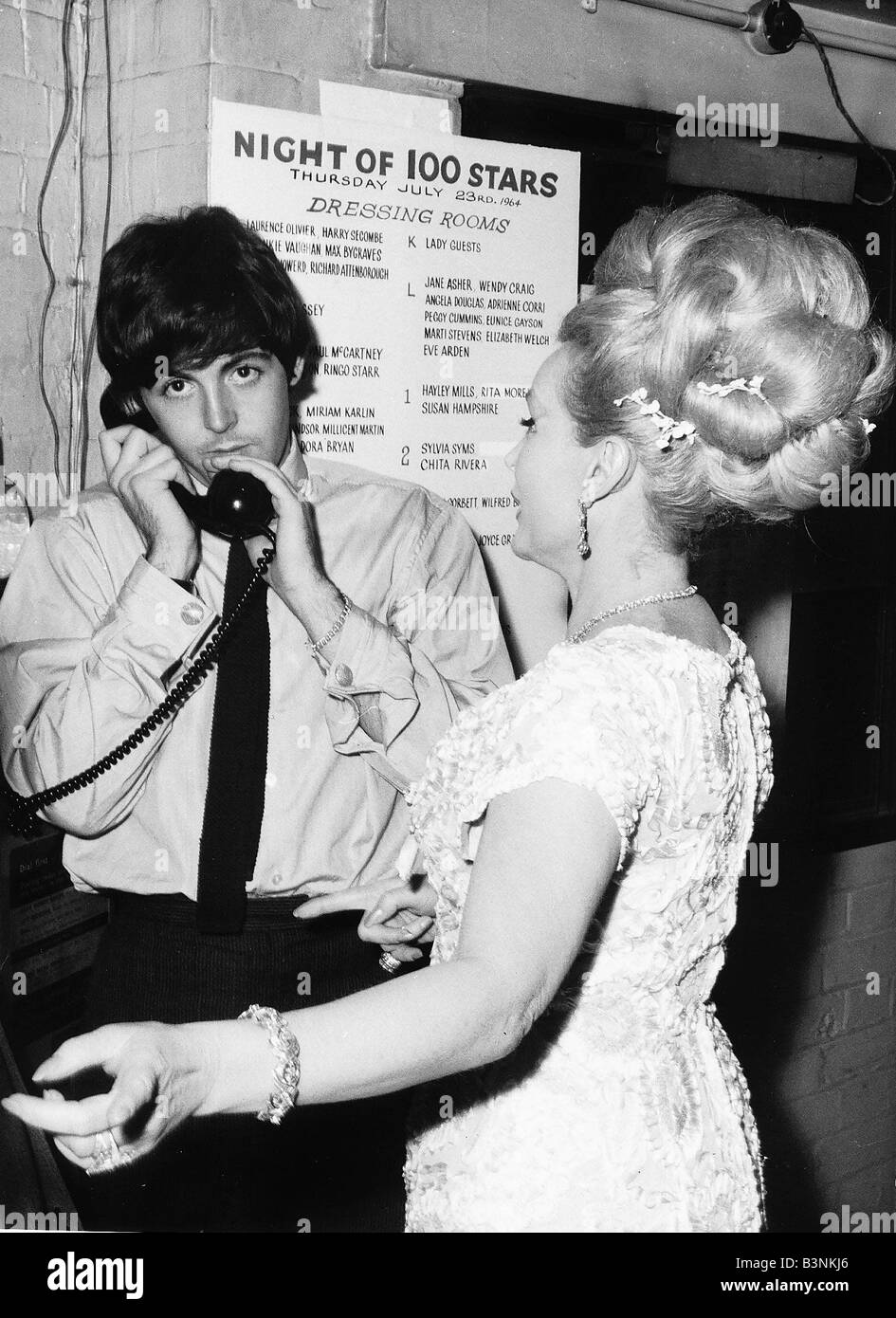 Paul McCartney Singer And Bass Guitar Player With The Beatles Talks On Phone While A Blonde Haired Lady Tries To Talk Him At Night Of Thousand