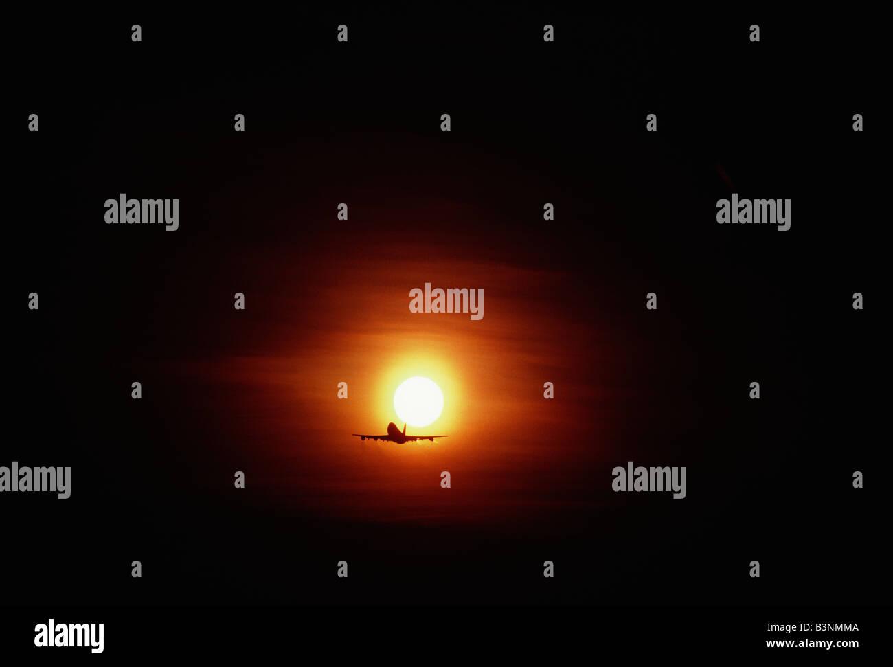 Commercial jetliner (Boeing 747 Jumbo Jet) flying into the setting sun - Stock Image