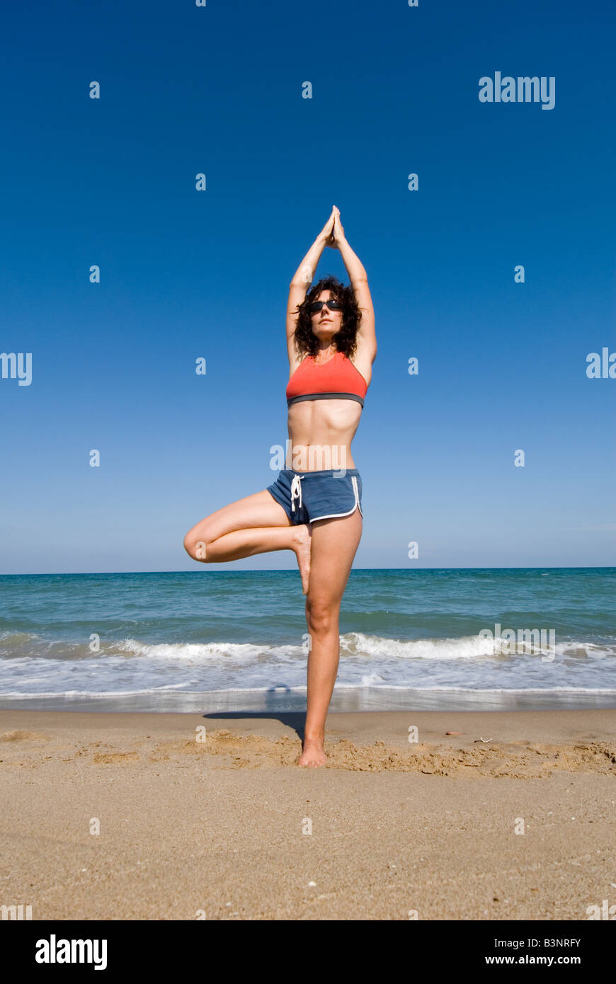 Model Released fit young woman doing yoga stretching stretching exercises on a sandy beach Stock Photo