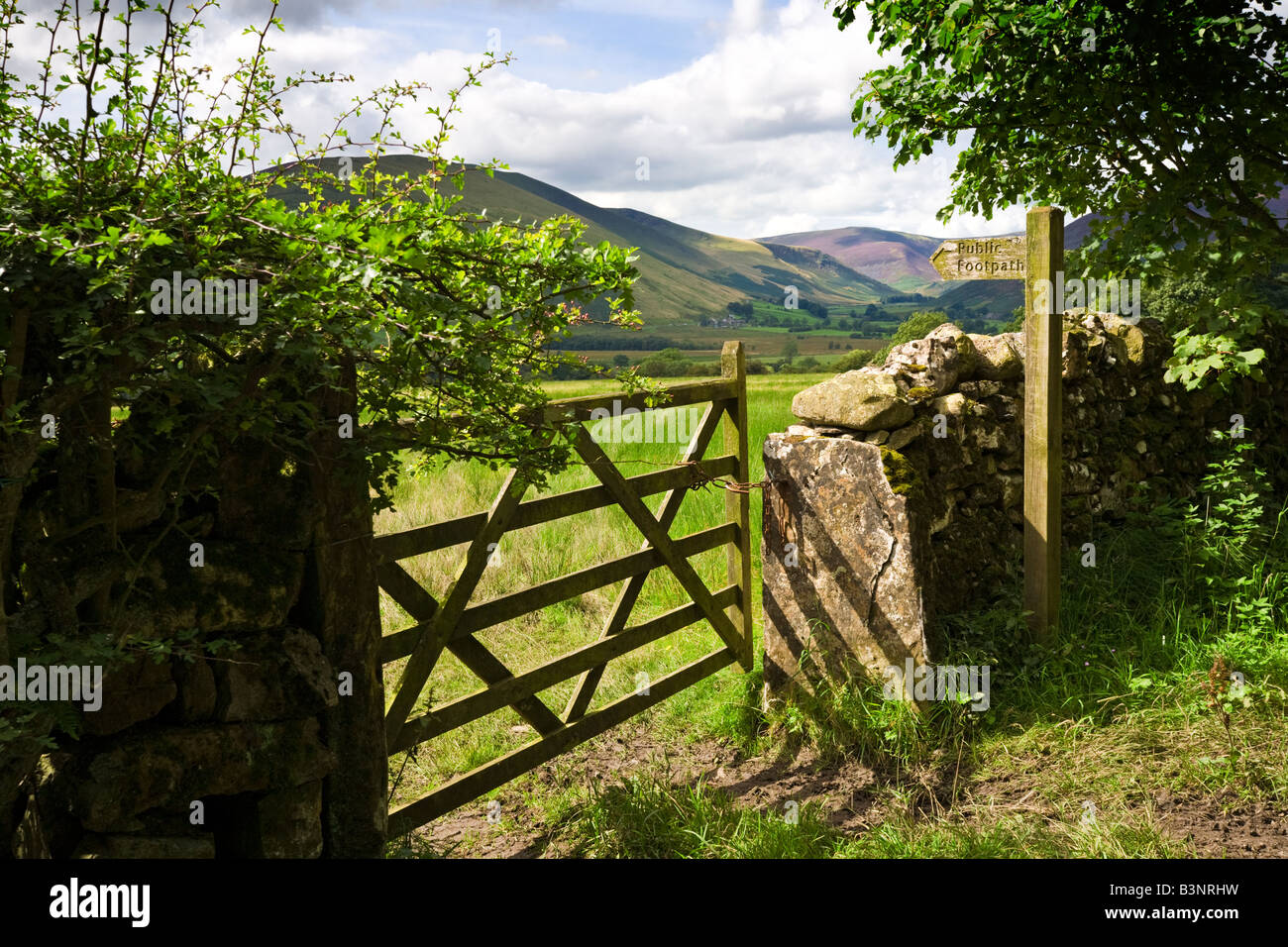 Typical English Lake District rural scene with wooden public footpath signpost sign, England, UK - Stock Image