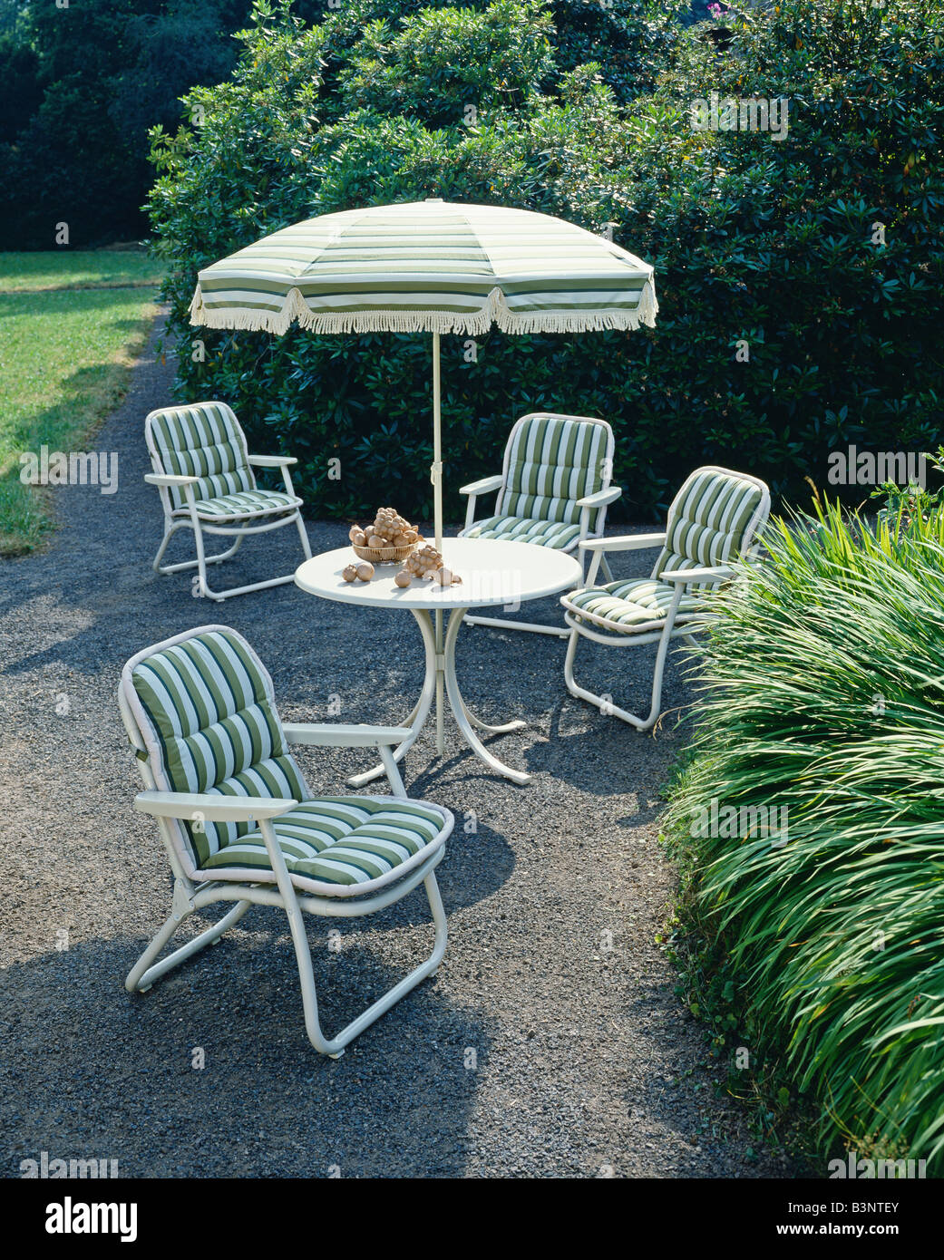GARDEN FURNITURE ARMCHAIRS AND PARASOL DECORATED WITH GREEN STRIPED FABRIC