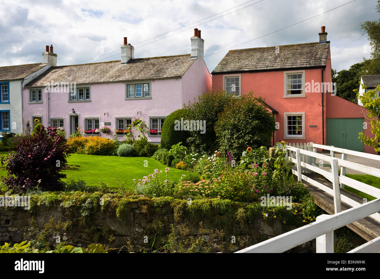 Pretty traditional painted cottages with bridge and colourful gardens in Caldbeck the Lake District England UK - Stock Image