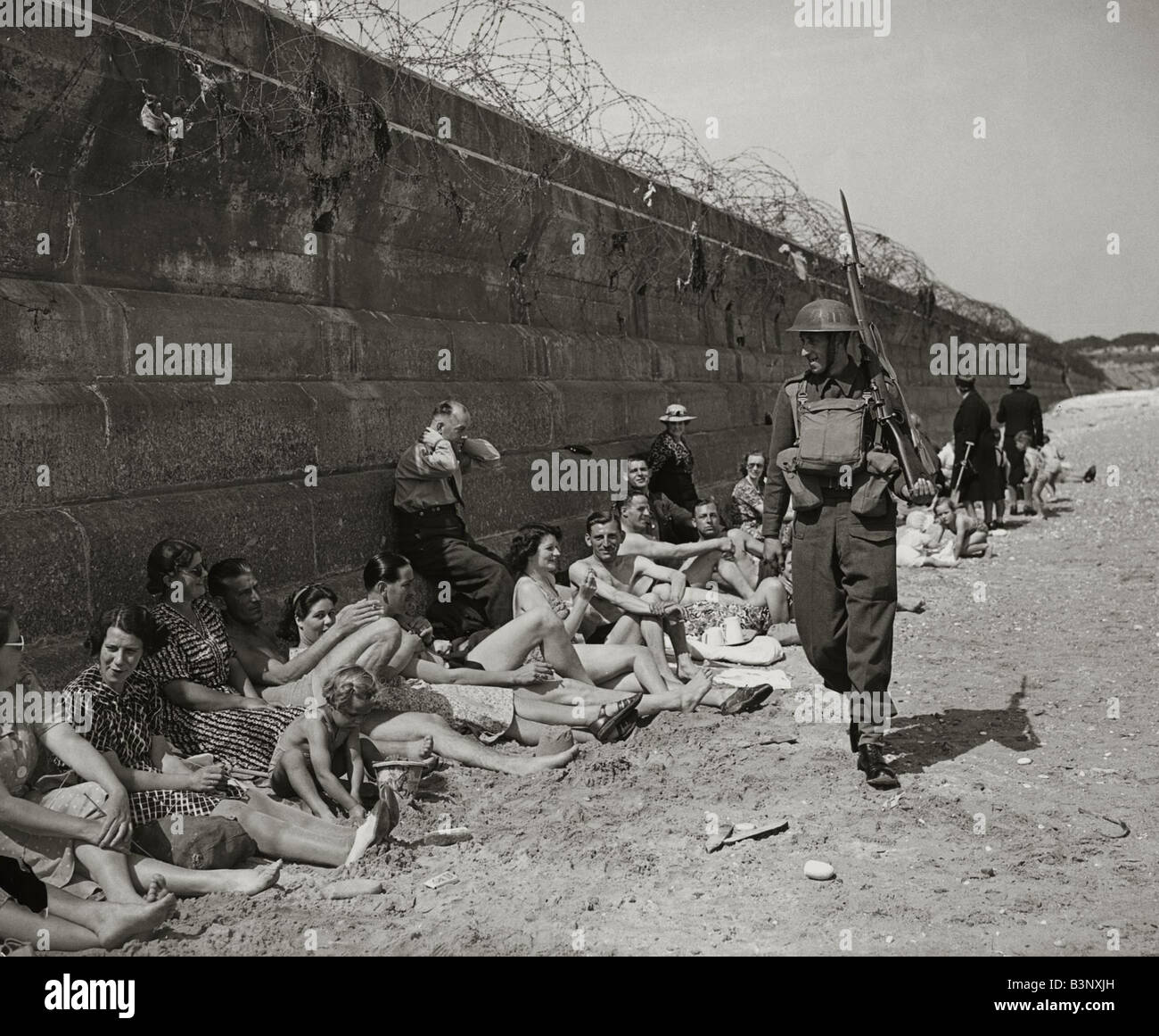 Holidaymakers sunbathing look pityingly at a passing home front serviceman carrying a rifle and bayonet wearing - Stock Image